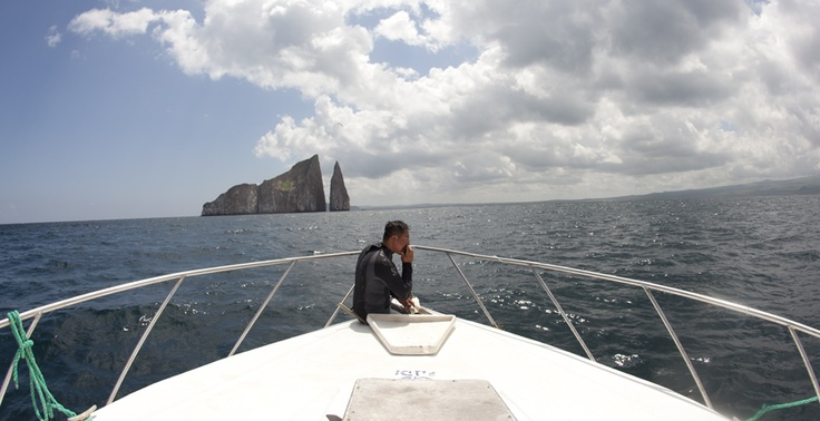 """Angel Quimi, of San Cristóbal, Galápagos Islands, Ecuador, waits to lower the anchor of his boat near """"Leon Dormido,"""" or, """"Kicker Rock."""" The rock is a prime destination for divers visiting the Islands, and Quimi, a divemaster, takes groups of snorkelers and divers there almost daily. Julia Wall/reesenews"""