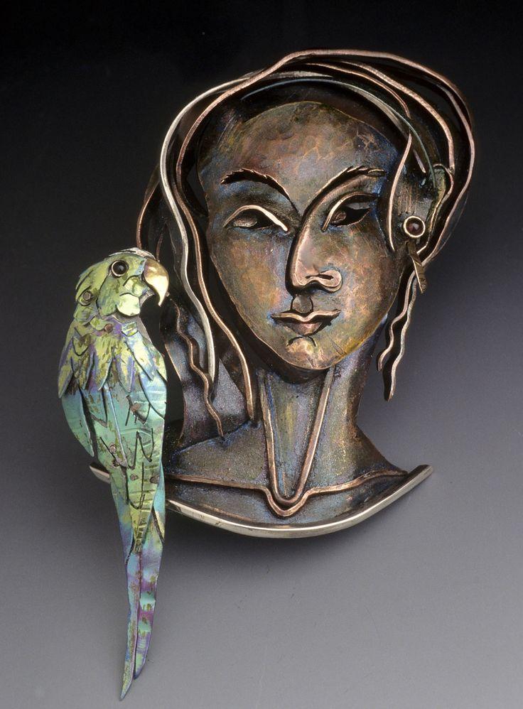 Brooch | Enid Kaplan.  'Guacamaya'.  14k gold, sterling silver, copper, niobium, onyx and garnet. 1999.