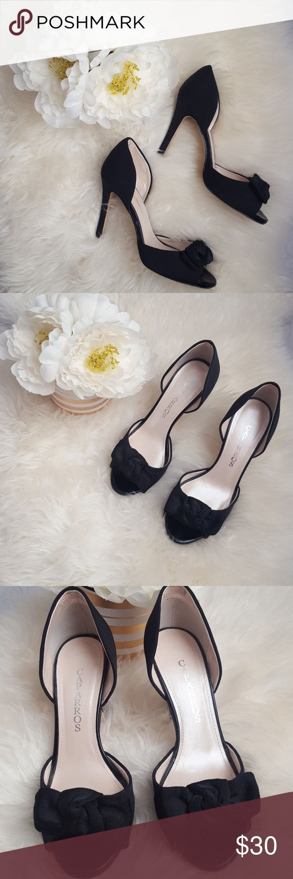 Pretty black heel with bow Shoe is in good condition overall with wear on the bottom of the heel. Open toe heel with bow. Caparros Shoes Heels
