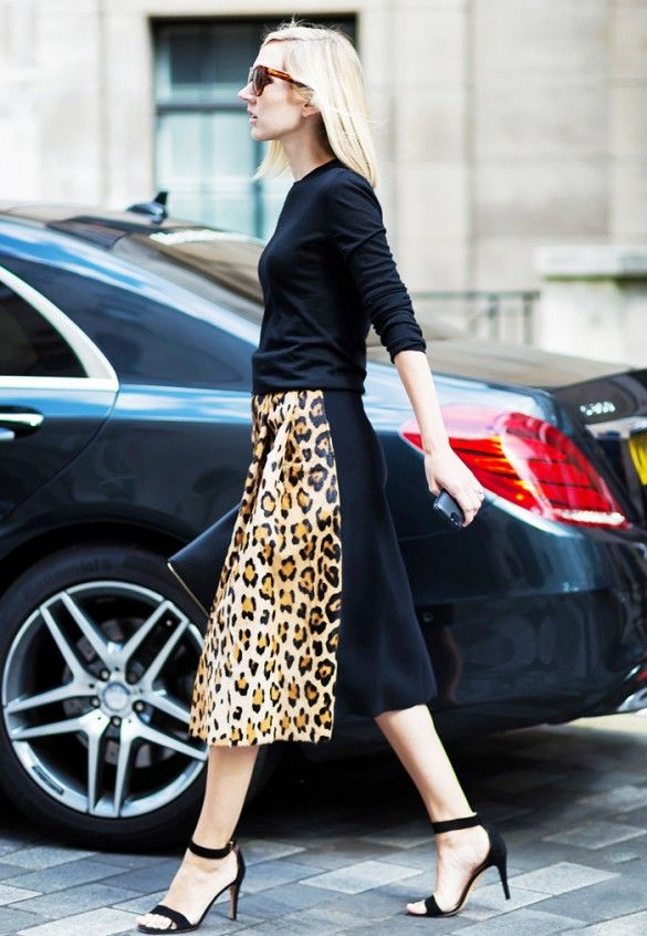 A black sweater is paired with a leopard print midi skirt and black ankle-strap sandals: