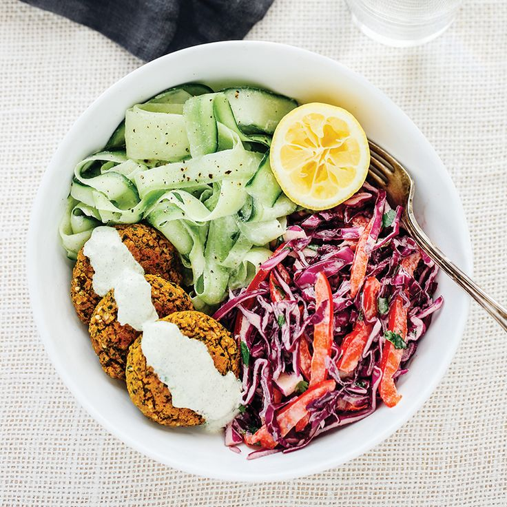 Prep Time: 40 Minutes | Cooking Time: 30 MinutesServes 4 Savory oven-baked falafel are balanced by tangy purple cabbage and red pepper slaw, cucumber noodles, and tzatziki sauce in this colourful dish. This dynamic trio is a plant-powered force of nourishment, simultaneously hearty and refreshing.