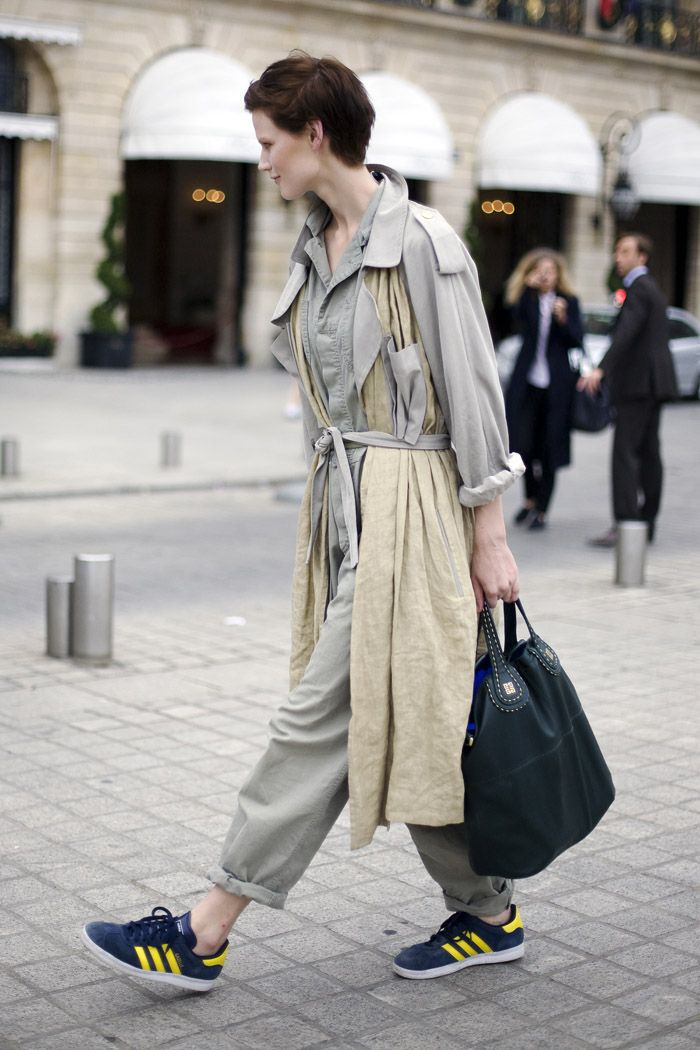 Saskia de Brauw in DEREK LAM trench, CALVIN KLEIN jumpsuit, black GIVENCHY bag, and blue & yellow ADIDAS sneakers.