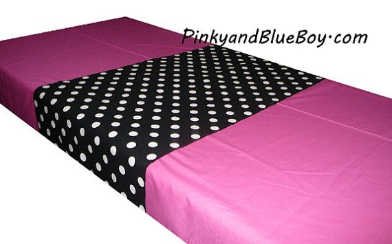 Minnie Mouse birthday party decorations . Black and white polka dot wrapping paper over a pink tablecloth.