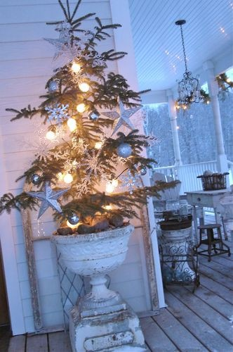 urn and tree with lights on the porch