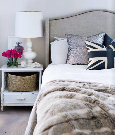 interior design bedroom with faux fur throw, white table lamp, upholstered bed head, shabby chic side table, sequin pillow cushion, british flag pillow