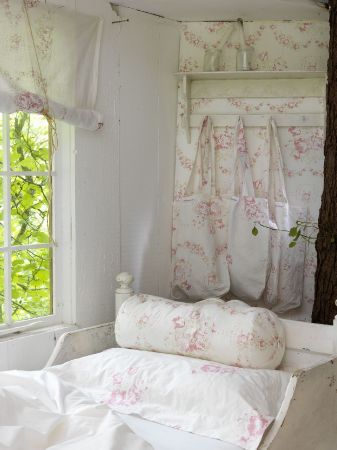 Cabbages and Roses - Cabbages and Roses Fabric Collection - Pretty light pink florals covering white wallpaper, blinds, fabric bags, a pillow and a bolster cushion on a white bed
