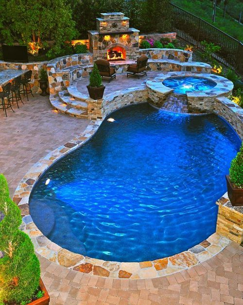 Stoned patio with built in pool and hot tub that cascades into the pool. Also a patio, fire place and bar area for entertaining #cherylkhan