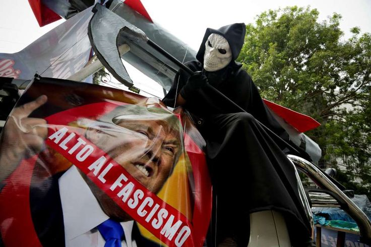 "May Day around the world  -  May 1, 2017:      A man dressed as the Grim Reaper sits over a banner of US President Trump that reads in Spanish: ""Stop fascism"" during the annual May Day parade in Panama City, Panama, on May 1, 2017."