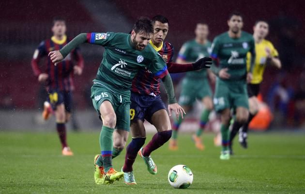 FC Barcelona's Alexis Sanchez, from Chile, third left, duels for the ball against Elche's Carles Gil during a Copa del Rey soccer ma...