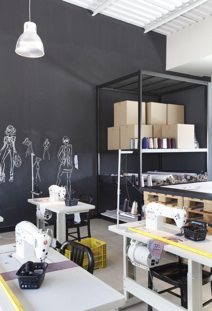 Sala com maquinas de costura e parede em forma de lousa para desenho com giz. By Gisele Tranto