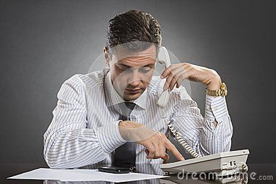 Successful businessman in white shirt with necktie picking up the receiver and dialing a phone number while sitting at his desk over grey background.