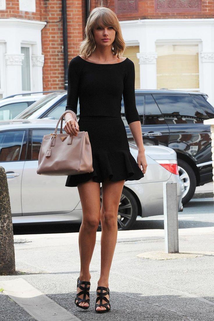 Taylor Swift - top y una falda de vuelo en color negro de Guess, unas sandalias altas con tiras de cuero y un bolso de Prada en color rosa empolvado.