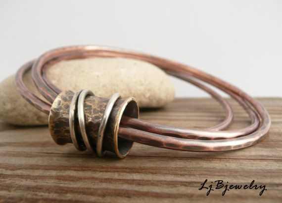 Copper Bangle, Mixed Metal Bangle, Stacking Bangle, Triple Bangle,Copper, Brass, Sterling Silver, Metalsmith Jewelry, Handmade   For the bangle lovers out there this bracelet is made of copper, red brass, and sterling silver. The red brass spinner ring holds together 3 copper bangles made of 10 gauge copper wire. Three sterling silver rings also spin around the red brass ring. The red brass tube is approximately 1,5cm long (0.58 inch) and 1 cm wide (0.39 inch) The bangles have been hammer…