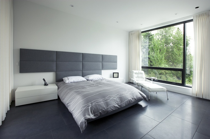 a spare bedroom in the hannon richards ferrier_webb residence located off of elbow drive, calgary is a serene balance of light walls and furniture floating on a dark floor / residential / davignon martin architecture + interior design