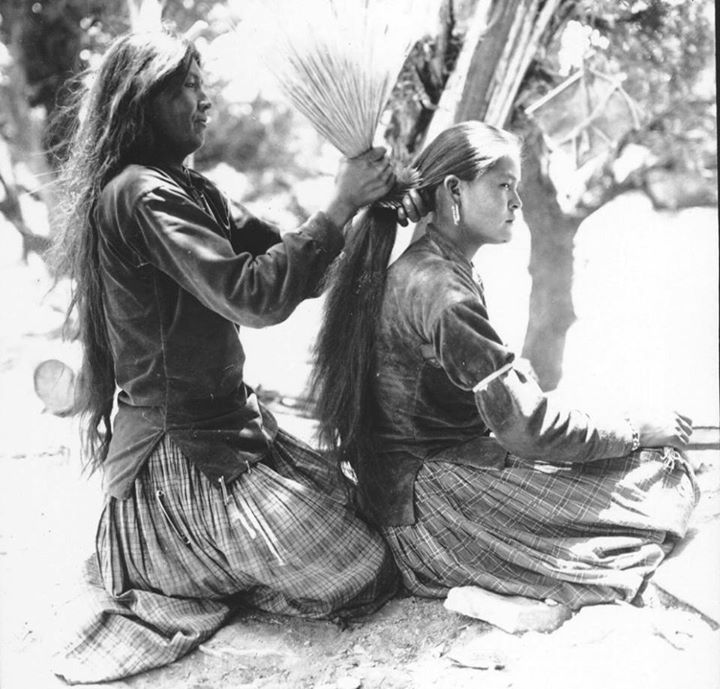 Navajo (Diné) mother tying her daughter's hair using brush. (1920s?).: