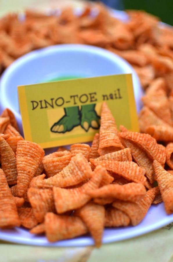 Dino Toe-nails. Nodig: Bugles chips. Dipsausje, Kaartje met dinopoten + tekst Dino Toenails. Werkwijze: Vul een schaal met Bugles chips, zet ertussen een schaaltje met dipsaus. Zet het kaartje ernaast zodat het duidelijk is wat de snack is.
