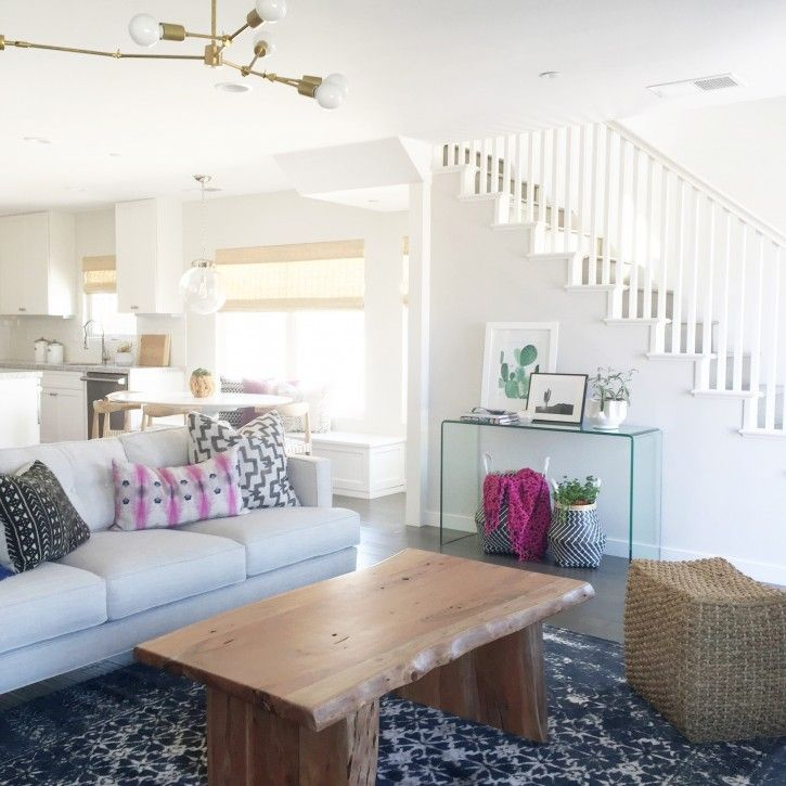love the live edge coffee table in front but contrasted with a light as air glass console table near the stairs interior design by becki owens