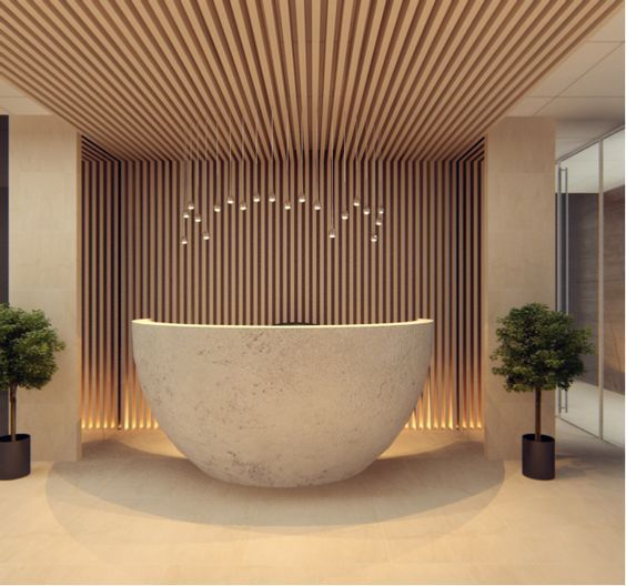 Beautiful round concrete reception desk, also love the timber cladding runs from wall to ceiling!!: