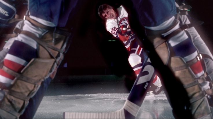 Promotional portrait of Canadian professional ice hockey player Mike Bossy of the New York Islanders as he shoots at goal, as seen through the legs of the goalie, early 1980s