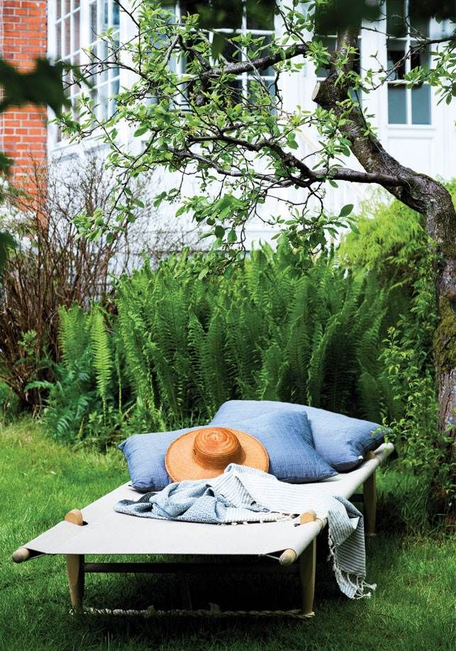 Kristinas terrasse bagerst i haven var glemt og forladt. Nu er den indrettet som et hyggeligt uderum midt i den frodige grønne have, hvor græsset får lov til at gro vildt.