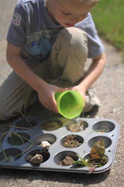 This photo shows a child engaged in play with a patty cake tin, he is using nature in each of the sections and is pouring water in to each of them.