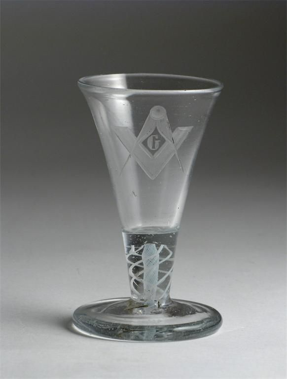 A Masonic firing glass late 18th / early 19th century, engraved with a set square and pair of compasses around the letter G, raised on a double series opaque twist stem and thick foot, 11cm.