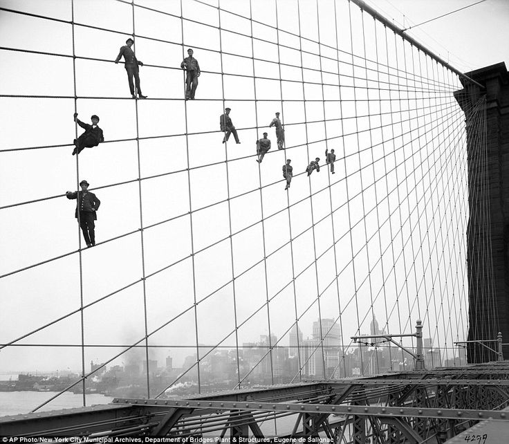 Painters hang from suspended wires on the Brooklyn Bridge October 7, 1914 -- 31 years after it first opened