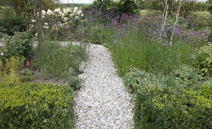 Der Weg aus den großen, hellen Kieseln schlängelt sich elegant durchs Gras