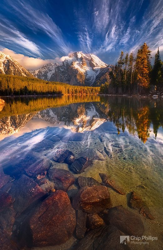 Early morning cloud reflections over Mount Moran on Leigh Lake in Grand Teton National Park backcountry.
