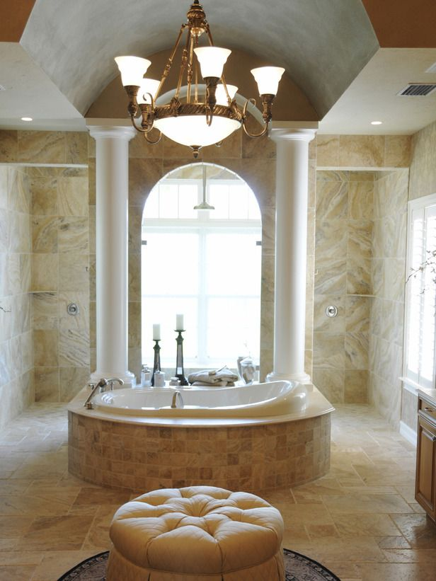 Designer Bathrooms Fit for Royalty: The neutral color palette and tranquil surroundings give this luxurious master bathroom a spa-like feel. With an abundance of natural light and outside views, bathing instantly feels more alfresco than enclosed. High ceilings, support columns and an elegant bronze chandelier visually expand the master bathroom, adding to the overall extravagance and refined look of the entire space.