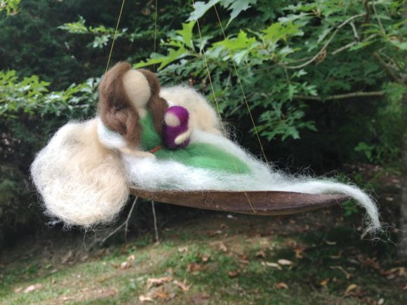 Fada-mãe com bebê no colo sentada. A fada e o bebê foram feitos em lã, por meio da técnica de feltragem à seco, utilizando apenas lã de ovelha e agulha para feltrar. Fazemos em outras cores sob encomenda.