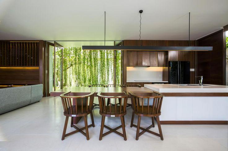 Cozinha com piso cinza, bancada em ilha emendada com mesa de jantar de madeira, cadeiras de madeira, sofá cinza, luminária pendente preta retangular, cortina verde. Casa Moderna + Jardim no Vietnã por MIA Design Studio
