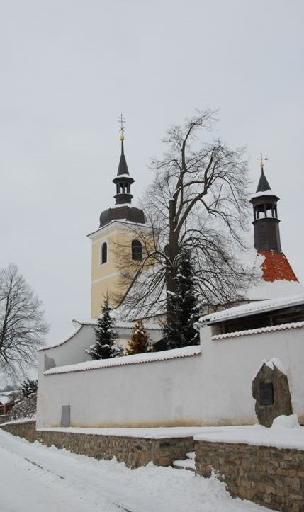 Louňovice pod Blaníkem (Benešov district, Central Bohemia), Czechia - the church of The Ascension of Holy Virgin Mary and the memorial plaque of famous baroque composer Jan Dismas Zelenka at his birthplace in the foreground