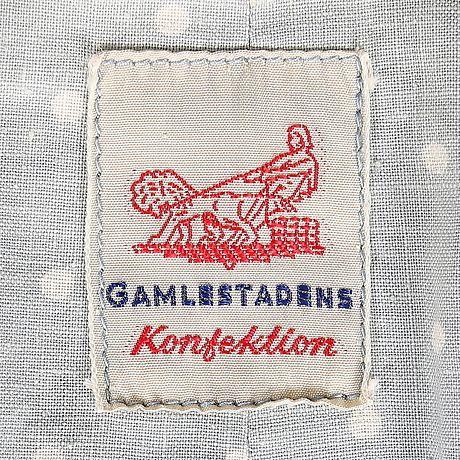 """Märkning i blå barnkappa med prickigt foder och rundad krage från """"Gamlestadens konfektion"""", ca 1950/60-tal."""
