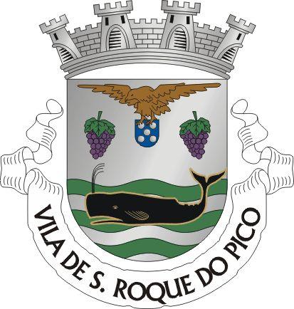 """Civic heraldry of Portugal - Brasões dos municípios Portugueses - Escudo de prata, com dois cachos de uvas de púrpura folhados e sustidos de verde. Em contra-chefe, três faixas ondadas de verde, em que nada uma baleia de negro realçada de ouro. Em chefe, um açor de sua cor realçado, voado, com uma quina de Portugal nas garras. Coroa mural de prata de quatro torres. Listel branco com a legenda a negro : """" VILA DE S. ROQUE DO PICO """".    on June 1, 1940."""