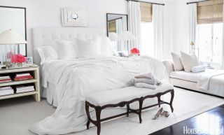 """""""I like the serenity of pure white linens and very soft, muted colors,"""" designer Brooke Davenport says of the master bedroom in her Los Angeles house. The custom headboard is upholstered in a Scalamandré linen, and the Minotti chaise longue is covered in a Donghia fabric. Custom nightstands and mirrors. Lamps, Ralph Lauren Home. Cocoon silk duvet over Sferra bed linens. Bone mirror above bed, JF Chen."""