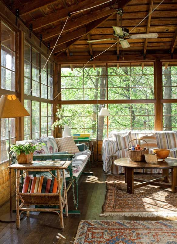 Afternoon light streams into the enclosed porch on the northwest corner, lakeside; the old ropes and pulleys are used to raise the windows.