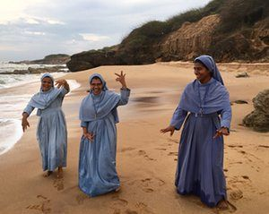 Student nuns having fun on the beach at Kanyakumari, Tamil Nadu. They are proudly demonstrating a traditional Tamil dance as the sun goes down.