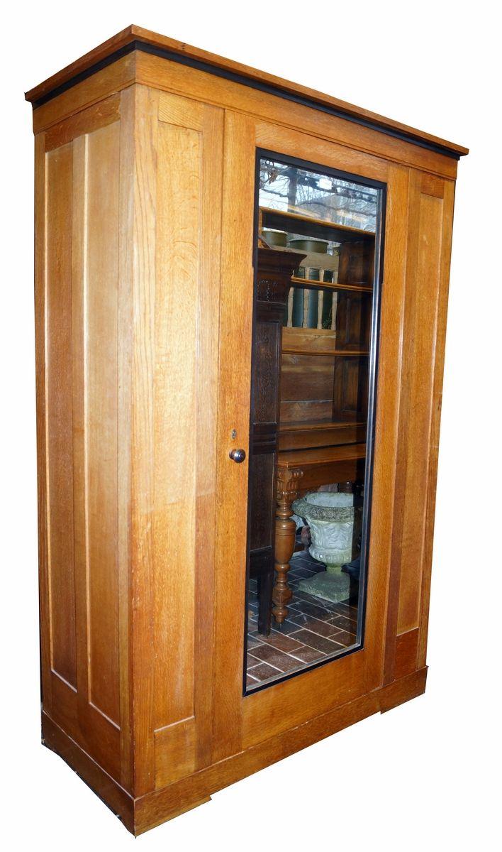 Een eikenhouten linnenkast met zwarte biezen en spiegeldeur waarachter legplanken met 1 lade, ca. 1930