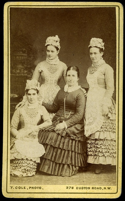 Studio portrait of a mistress with three maids, inscribed in ink on the verso, 1882.