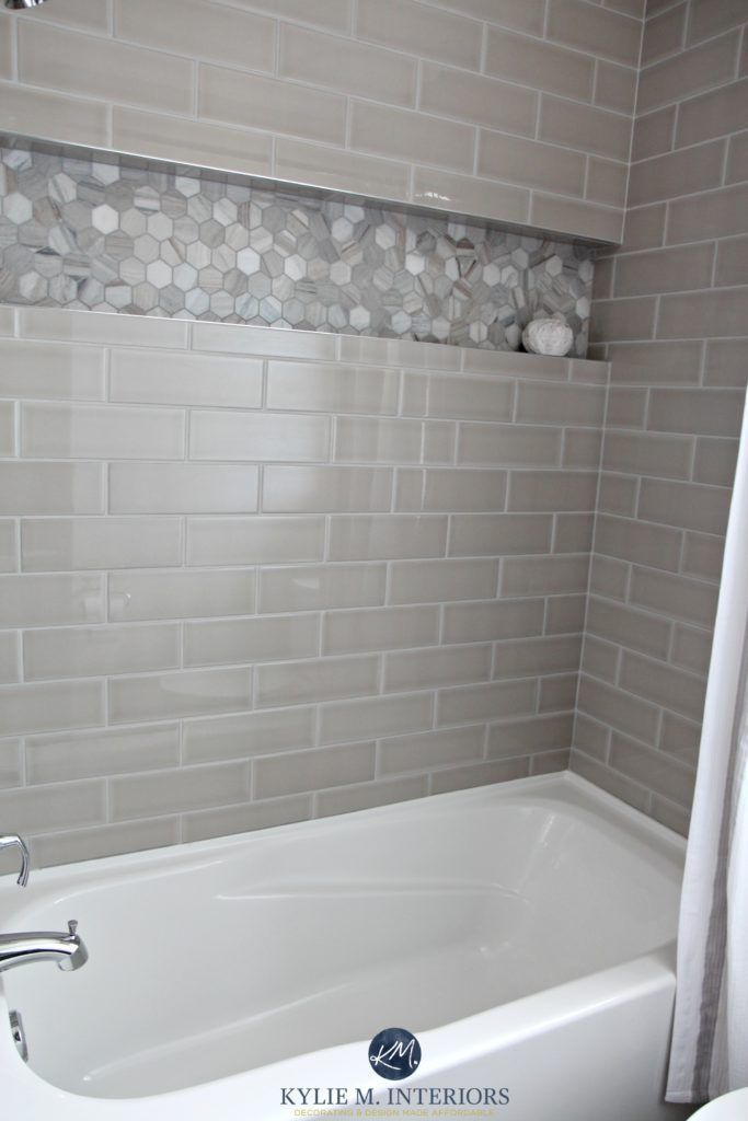 bathroom with bathtub and gray subway tile shower surround with niche or alcove in hexagon marble - Shower Wall Tile Designs