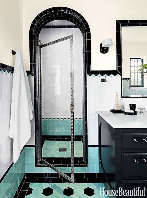 Colorful bathroom. The fabulous shower door is the only piece original to the room. Showerhead by Newport Brass in polished nickel. Selma Streamline sconce with Clamshell Opal shade and black porcelain towel hooks from Rejuvena-tion. Anichini towel.