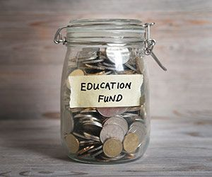 A glass jar full of coins with tape on its side reading 'Education Fund'