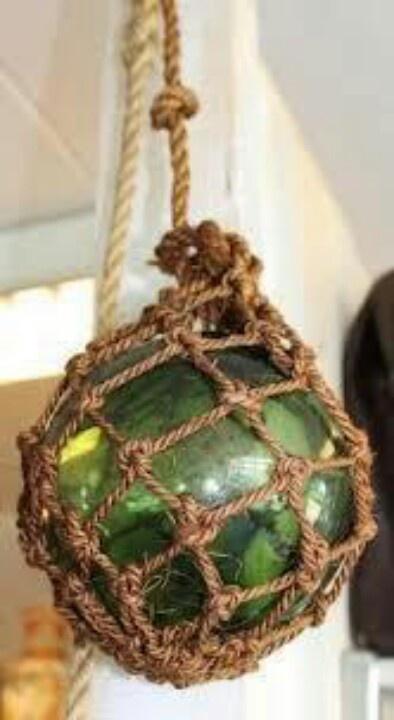 Donker Nautische kleuren....(bruin, groen, oranje) en visnetten met heksenbollen aan het plafond....in de tuin.....met lamp erin...