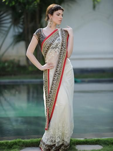 A netted #Saree with sequin and stone work and a contrasting border accompanied by a ready made brocade blouse.