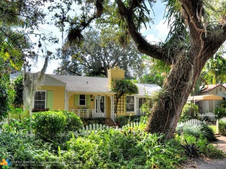 This Miami tiny home has painted yellow wood siding, a front porch, chimney, gable roof and adorable green shutters. Click through to see more of this Colee Hammock Cottage.