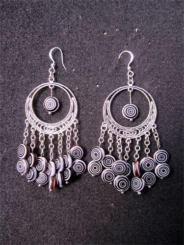 Spiral - 12    Långa örhängen med cirkelformat fäste och detaljer i silverpläterad metall. Hängande glaspärlor i Svart/Vit Spiralmönster samt nickelfria krokar. Frakten är inkluderad i priset.    Pris:  210 kr