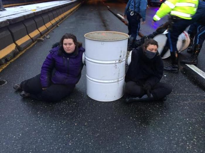 "In this photo provided by the Massachusetts State Police, protesters sit near a barrel in a northbound lane during morning rush hour on Interstate 93 in Milton, Mass., Thursday, Jan. 15, 2015. The Boston contingent of Black Lives Matter said in a statement that the protest was intended ""to confront white complacency in the systemic oppression of black people in Boston."" (AP Photo/Massachusetts State Police)"