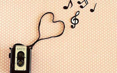 Un caset con su cinta formado de corazón y notas musicales arriba..