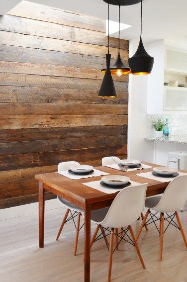 Scandinavian style dinning room with barn wood accent wall; Eames chairs, Tom Dixon pendant lights; white interior; Mid-century modern furniture; teak table; white kitchen; open space.